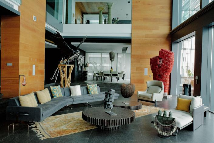 Two Sculptures, an eagle by Wim Botha and a colossal red piece by dominique Zinkpè, dominate one end of the <br> living room. Jérôme Abel Seguin cocktail tables.