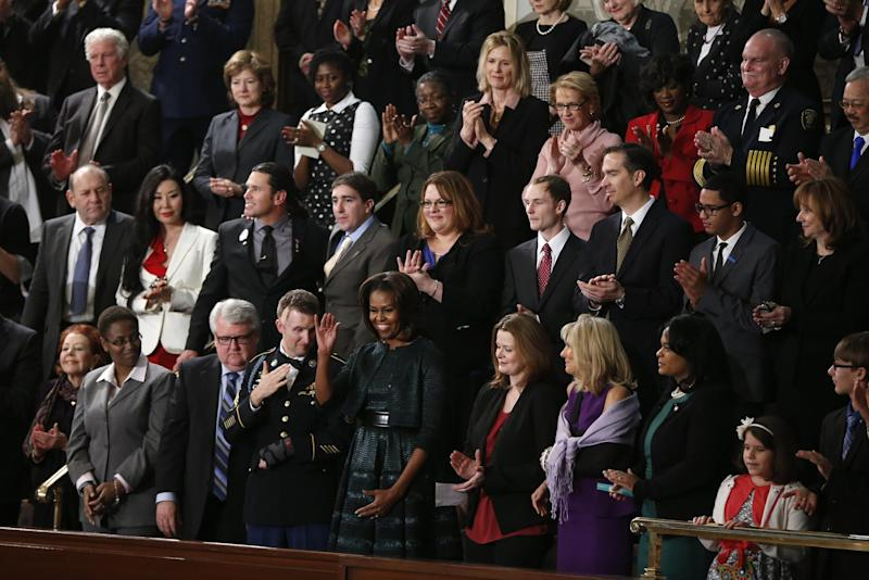** ADDS NAMES ** First lady Michelle Obama waves as she arrives for President Barack Obama's State of the Union address on Capitol Hill in Washington, Tuesday Jan. 28, 2014. Front row, second from left are, Sabrina Simone Jenkins, Craig, Remsburg, Sgt. 1st Class Cory Remsburg, first lady Michelle Obama, Misty DeMars, Jill Biden, Kathy Hollowell-Makle, Aliana Arzola-Pinero and Joey Hudy. Second row, third from left are, Jeff Bauman, Carlos Arredondo, Amanda Shelly, Nick Chute, John Soranno, Estiven Rodriguez, and General Motors CEO Mary Barra. Third row, second from right are, Antoinette Tuff, and Moore (Okla.) Fire Chief Gary Bird, right. (AP Photo/Charles Dharapak)