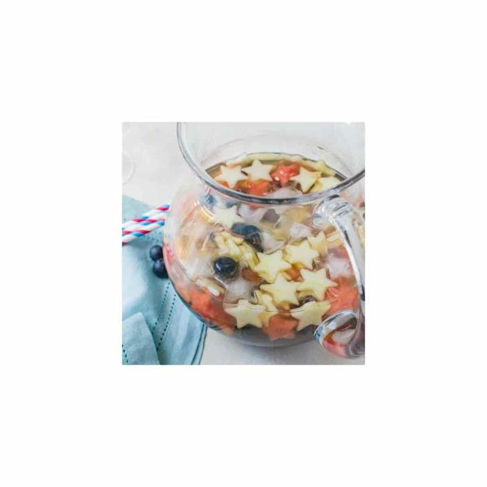 """<p>Give white sangria an upgrade fit for the Fourth of July by slicing up the fruit with a star-shaped cookie cutter. </p><p>Get the <a href=""""https://www.garlicandzest.com/red-white-and-blue-sangria/"""" rel=""""nofollow noopener"""" target=""""_blank"""" data-ylk=""""slk:recipe"""" class=""""link rapid-noclick-resp"""">recipe</a>.</p>"""