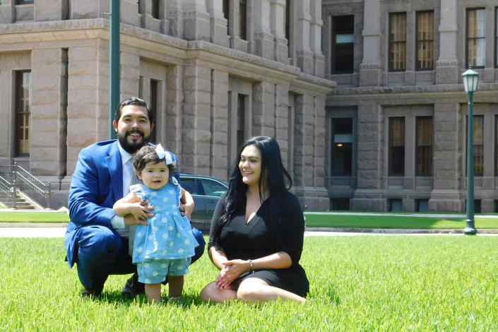 Donovon Rodriguez, chief of staff for Texas state Rep. Ray Lopez, poses on the grounds of the Texas capitol with his wife, Jenny Tavarez, and daughter, Evelyn Belle Rodriguez, for whom he is the sole provider, Monday, July 26, 2021, in Austin, Texas. Rodriguez could lose his job by Sept. 1, 2021, if legislative budget funding is not restored. (AP Photo/Acacia Coronado)