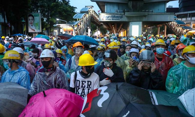 Pro-democracy protesters wearing helmets in Bangkok
