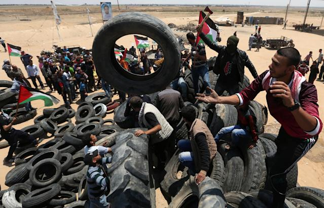 <p>Palestinians collect tires to be burnt during a protest marking the 70th anniversary of Nakba, at the Israel-Gaza border in the southern Gaza Strip, May 15, 2018. (Photo: Ibraheem Abu Mustafa/Reuters) </p>
