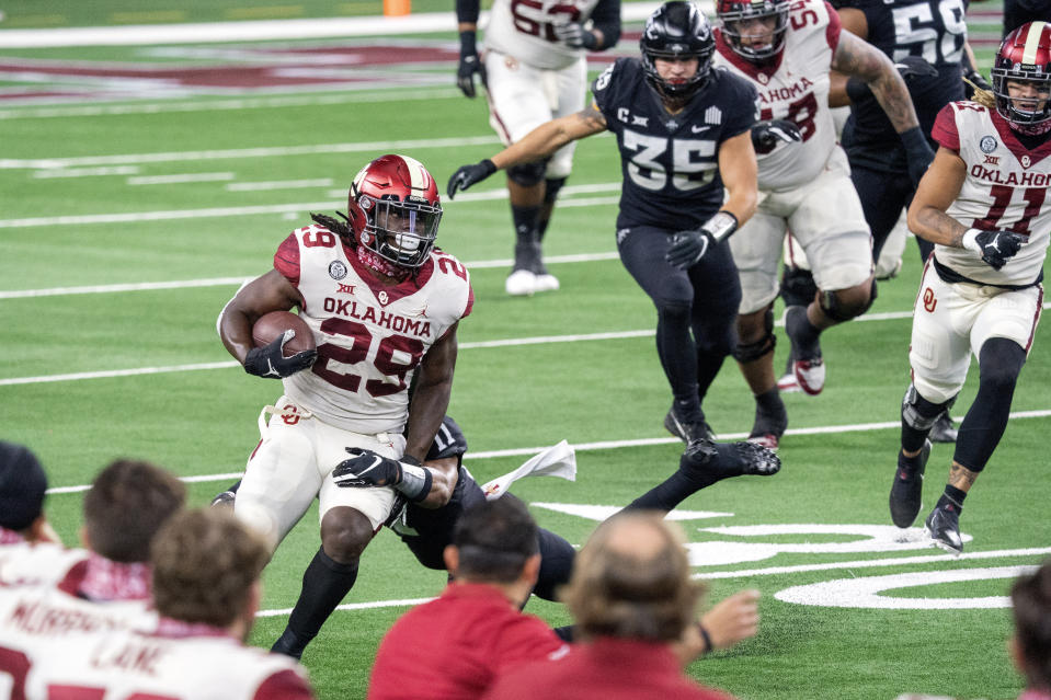 Oklahoma running back Rhamondre Stevenson (29) turns the corner past Iowa State defensive back Lawrence White IV (11) during the first half of the the Big 12 Conference championship NCAA college football game, Saturday, Dec. 19, 2020, in Arlington, Texas. (AP Photo/Jeffrey McWhorter)