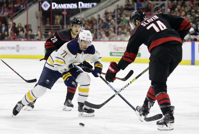 Buffalo Sabres' Evan Rodrigues (71) skates between Carolina Hurricanes' Sebastian Aho (20), of Finland, and Jaccob Slavin (74) during the first period of an NHL hockey game in Raleigh, N.C., Saturday, March 16, 2019. (AP Photo/Gerry Broome)