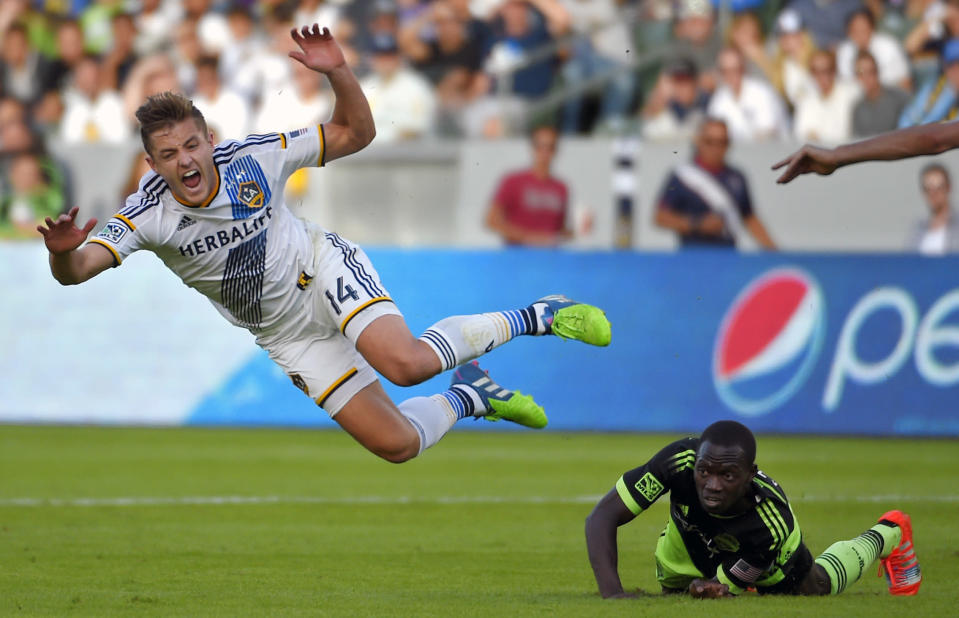 Los Angeles Galaxy midfielder Robbie Rogers, left, jumps over Seattle Sounders midfielder Micheal Azira during the second half of an MLS soccer playoff game, Sunday, Nov. 23, 2014, in Carson, Calif. The Galaxy won 1-0. (AP Photo/Mark J. Terrill)