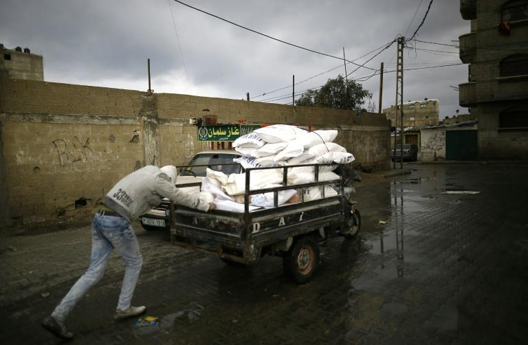 A Palestinian man pushes a cart with food aid in Gaza City on January 17, 2018