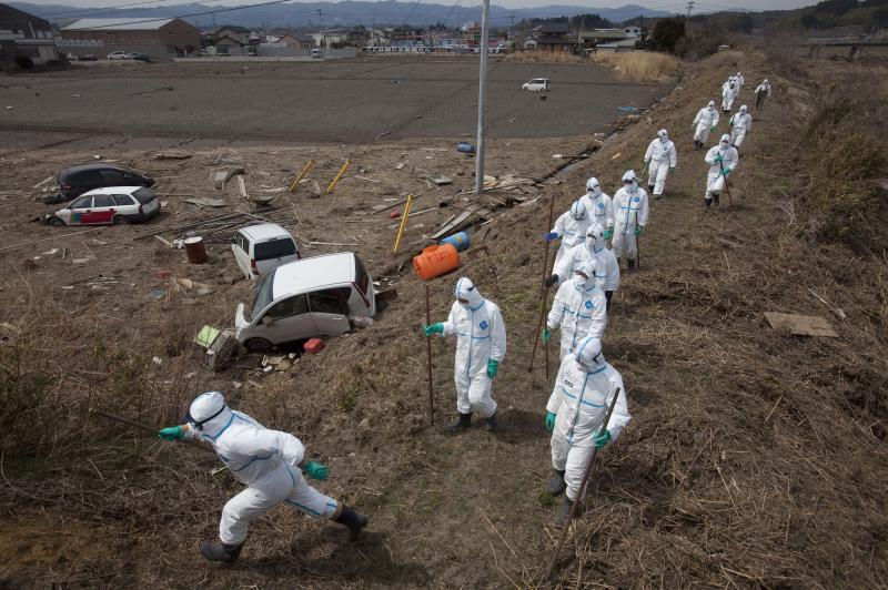 FILE - In this April 7, 2011 file photo, Japanese police, wearing suits to protect them from radiation, search for victims inside the deserted evacuation zone, established for the 20 kilometer radius around the Fukushima Dai-ichi nuclear reactors, in Minamisoma, Fukushima prefecture, Japan. People exposed to the highest doses of radiation during the Fukushima nuclear plant disaster in 2011 may have a slightly higher risk of cancer that is so small it probably won't even be detectable, according to a new report from the World Health Organization released on Thursday Feb. 28, 2013. (AP Photo/David Guttenfelder, File)