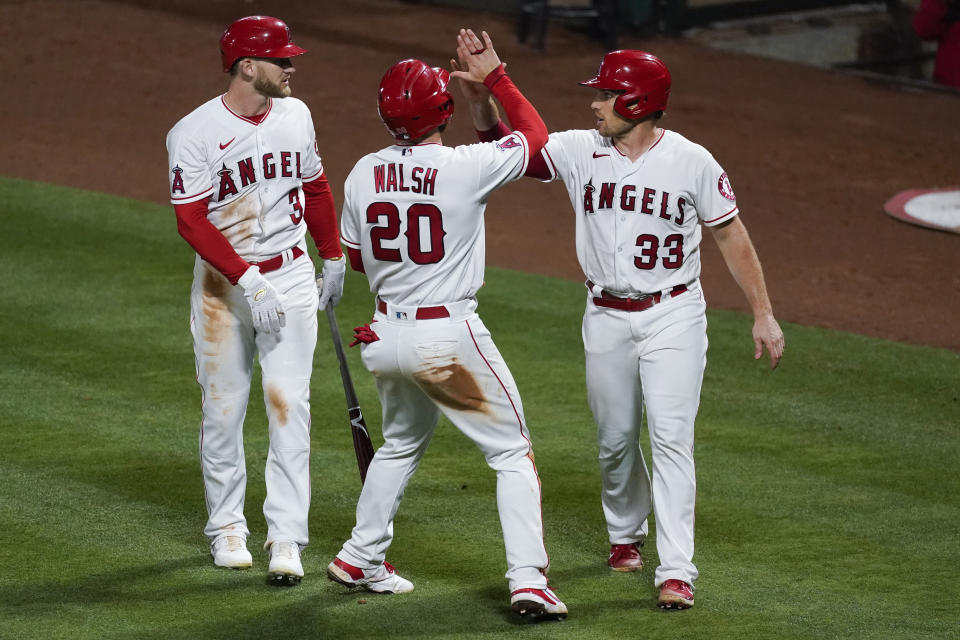 Los Angeles Angels' Jared Walsh (20) and Max Stassi (33) celebrate with Taylor Ward (3) after Walsh and Stassi scored off of single hit by Juan Lagares during the eighth inning of a baseball game against the Seattle Mariners Saturday, June 5, 2021, in Anaheim, Calif. (AP Photo/Ashley Landis)