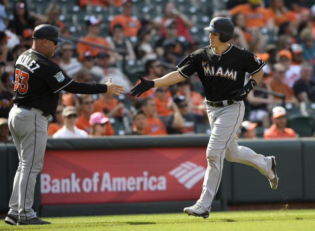 Miami Marlins' J.T. Realmuto, right, is greeted by third base coach Fredi Gonzalez (33) while rounding third on his two-run home run during the third inning of a baseball game against the Baltimore Orioles, Saturday, June 16, 2018, in Baltimore. (AP Photo/Nick Wass)