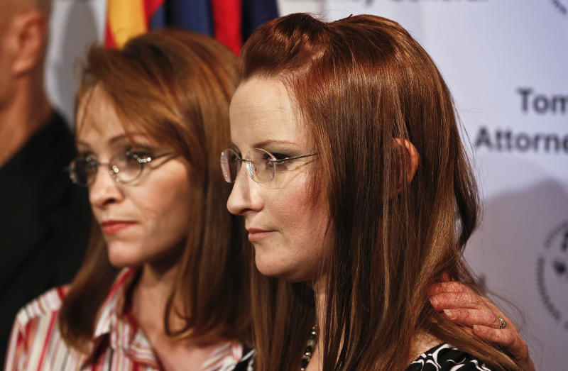 Flora Jessop, left, embraces her sister Ruby Jessop as they listen to Arizona Attorney General Tom Horne speak at a news conference, Tuesday, Jan. 22, 2013, in Phoenix. Horne discussed how his agency and others, including Flora helped Ruby and her six children leave a polygamist sect along the Utah-Arizona border. (AP Photo/Ross D. Franklin)