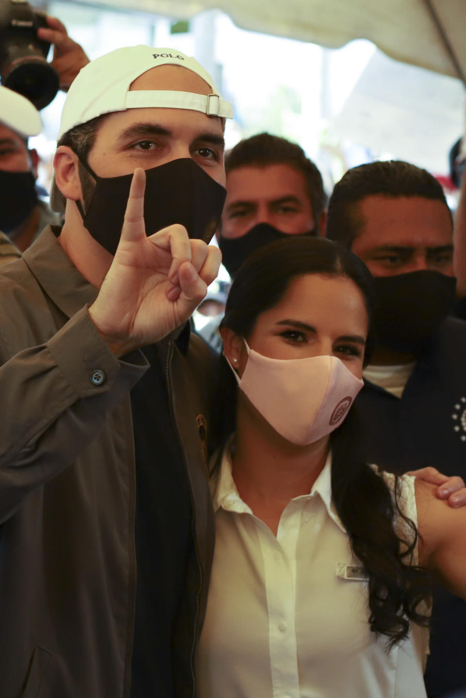 President Nayib Bukele holds up his marked finger after voting, as he poses with his wife Gabriela Rodriguez de Bukele at a polling station during local and legislative elections, in San Salvador, El Salvador, Sunday, Feb. 28, 2021. (AP Photo/Salvador Melendez)