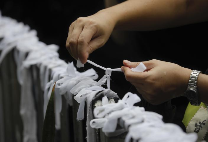 A pro-democracy protester ties a white-ribbon, symbolizing the pure intentions of young protesters during a march organized by teacher in Hong Kong Saturday, Aug. 17, 2019. China's paramilitary People's Armed Police marched and practiced crowd control tactics at a sports complex in Shenzhen across the border in Hong Kong on Friday, Aug. 16 in what some have interpreted as a threat against pro-democracy protesters. (AP Photo/Vincent Yu)