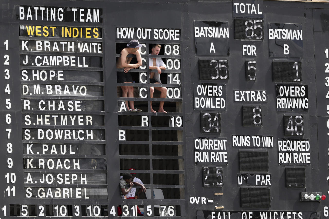 Spectators watch from the scoreboard on day four of the third cricket Test match between England and West Indies at the Daren Sammy Cricket Ground in Gros Islet, St. Lucia, on Feb. 12, 2019. (AP Photo/Ricardo Mazalan)