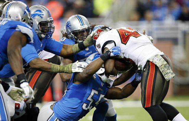 The Detroit Lions defensive line takes down Tampa Bay Buccaneers running back Bobby Rainey (43) during the third quarter of an NFL football game at Ford Field in Detroit, Sunday, Nov. 24, 2013. (AP Photo/Rick Osentoski)
