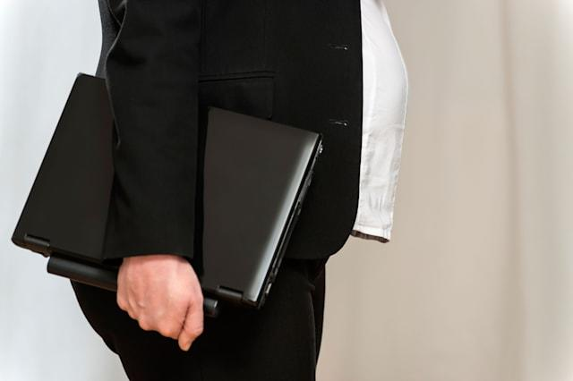 Pregnant blond business woman in black business clothing with laptop and light background