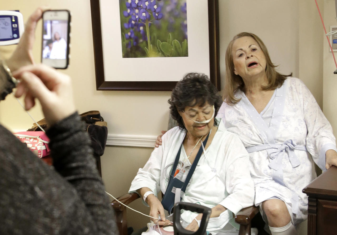 In this Jan. 14, 2014 photo. Irma Myers-Santana, left, and her sister Anna Williamson, right, sing a song as Kim Pappas films them with her cell phone in Houston. Earlier this month the sisters ended up in the same operating room, each getting one lung from the same donor. (AP Photo/Pat Sullivan)