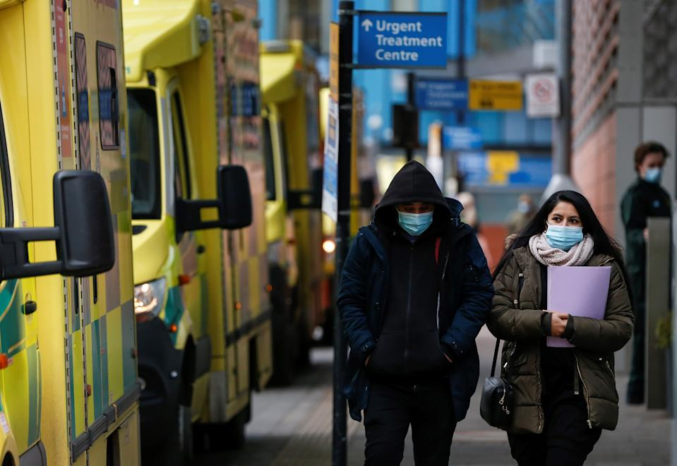 LONDON, Jan. 26, 2021 -- People wearing face masks walk past ambulances at The Royal London Hospital in London, Britain, on Jan. 26, 2021. The total number of coronavirus-related deaths in Britain has surpassed 100,000 after another 1,631 have been confirmed, according to official figures released Tuesday. The total number of coronavirus-related deaths in Britain now stands at 100,162, the data showed. (Photo by Han Yan/Xinhua via Getty) (Xinhua/Han Yan via Getty Images)