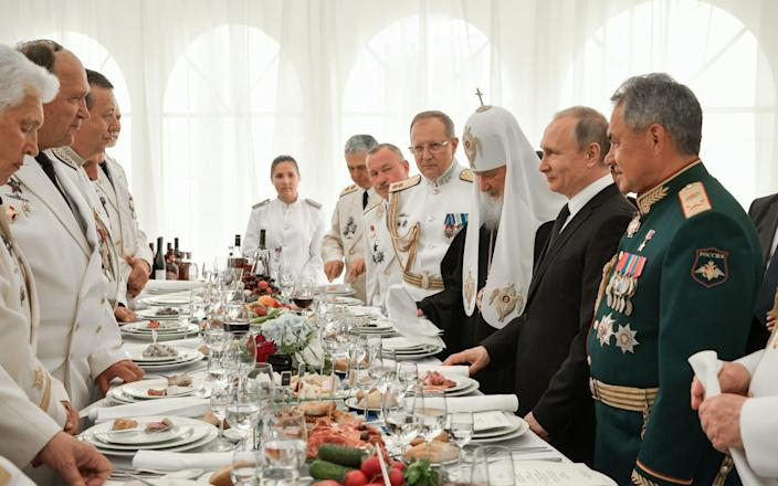 <span>Defence minister Sergei Shoigu, president Vladimir Putin, and Patriarch Kirill of Moscow and all Russia at a Navy Day reception </span> <span>Credit: Alexei Nikolsky\\TASS via Getty Images </span>