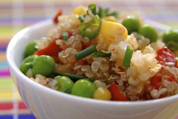 Colorful quinoa salad with corn, bell pepper and peas.