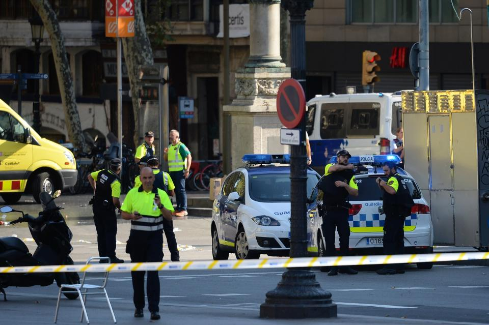 <p>Medical staff members and policemen stand in a cordoned off area after a van ploughed into the crowd, injuring several persons on the Rambla in Barcelona on August 17, 2017. (Josep Lago/AFP/Getty Images) </p>