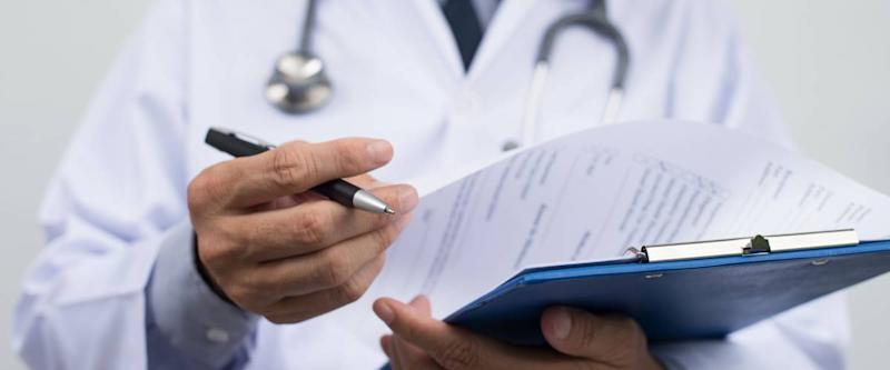 Male doctor on duty in white coat reading patient's information with pen in hand, filling prescription or checklist document, close up, selective focus on pen, health and medical concept.