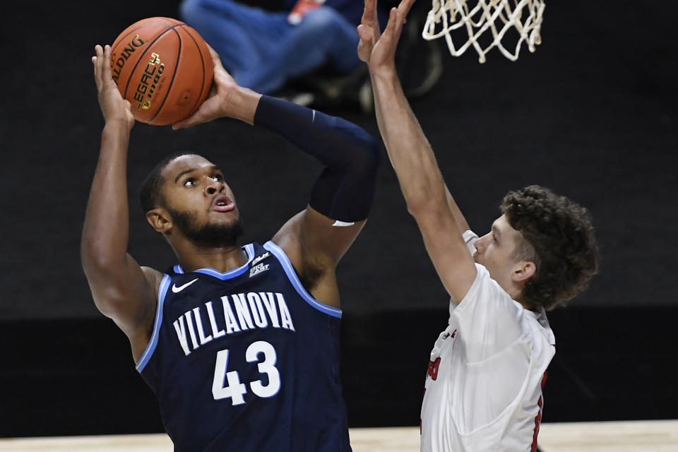 Villanova's Eric Dixon, left, shoots over Hartford's Hunter Marks in the first half of an NCAA college basketball game, Tuesday, Dec. 1, 2020, in Uncasville, Conn. (AP Photo/Jessica Hill)