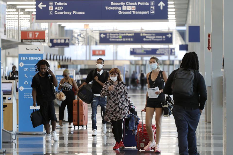 FILE - In this Tuesday, June 16, 2020, file photo, travelers walk through Terminal 3 at O'Hare International Airport in Chicago. Unions are gaining support in Congress for another $32 billion in federal aid to protect airline workers from layoffs for another six months. Still, it's too early to say how the issue will turn out. (AP Photo/Nam Y. Huh, File)