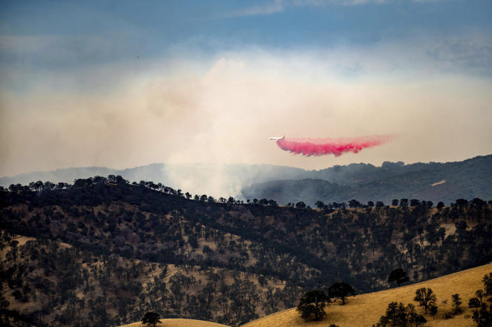 An air tanker drops retardant while battling one of several wildfires comprising the Deer Zone fires a unincorporated Contra Costa County, Calif., on Sunday, Aug. 16, 2020. Firefighters scrambled to contain multiple blazes, sparked by widespread lightning strikes throughout the region, as a statewide heat wave continues. (AP Photo/Noah Berger)