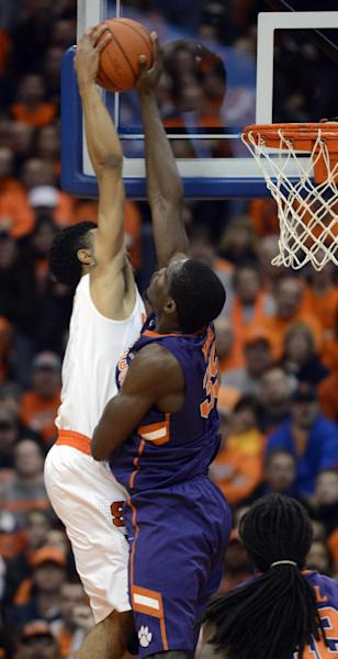 Syracuse's Michael Gbinije, left, has his shot rejected by Clemson's Landry Nnoko during the first half of an NCAA college basketball game in Syracuse, N.Y., Sunday, Feb. 9, 2014. (AP Photo/Kevin Rivoli)