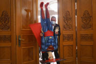 A man carries a mannequin depicting Superman ahead of a no confidence vote against Romanian Prime Minister Florin Citu's government in Romania's parliament in Bucharest, Romania, Tuesday, Oct. 5, 2021. (AP Photo/Andreea Alexandru)