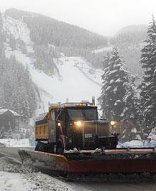 A snowplough clears a road on Monday, when the Men's super combined event was postponed due to bad weather