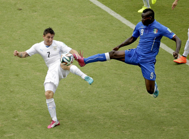 Italy's Mario Balotelli (9) and Uruguay's Cristian Rodriguez (7) battle for the ball during the group D World Cup soccer match between Italy and Uruguay at the Arena das Dunas in Natal, Brazil, Tuesday, June 24, 2014. (AP Photo/Hassan Ammar)