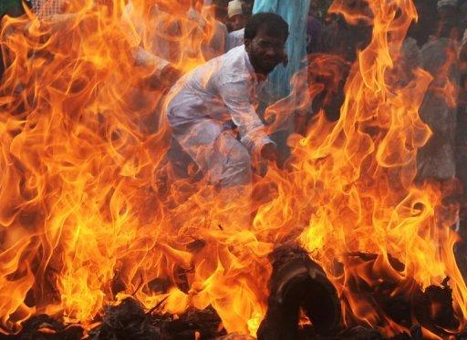 An Indian Muslim student hits a burning effigy of US President Barack Obama as others shout anti-US slogans