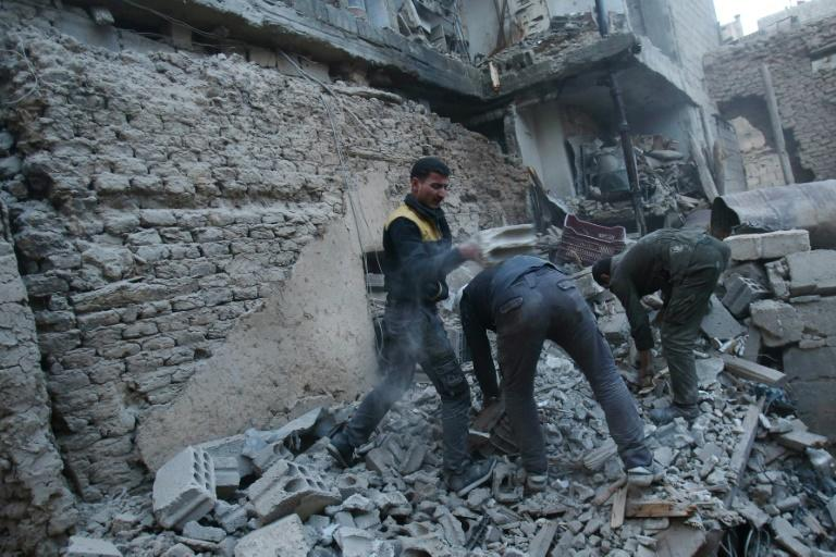Syrian civil defence forces, known as the White Helmets, search for victims following an airstrike on the rebel-held enclave of Arbin in Eastern Ghouta near the capital Damascus