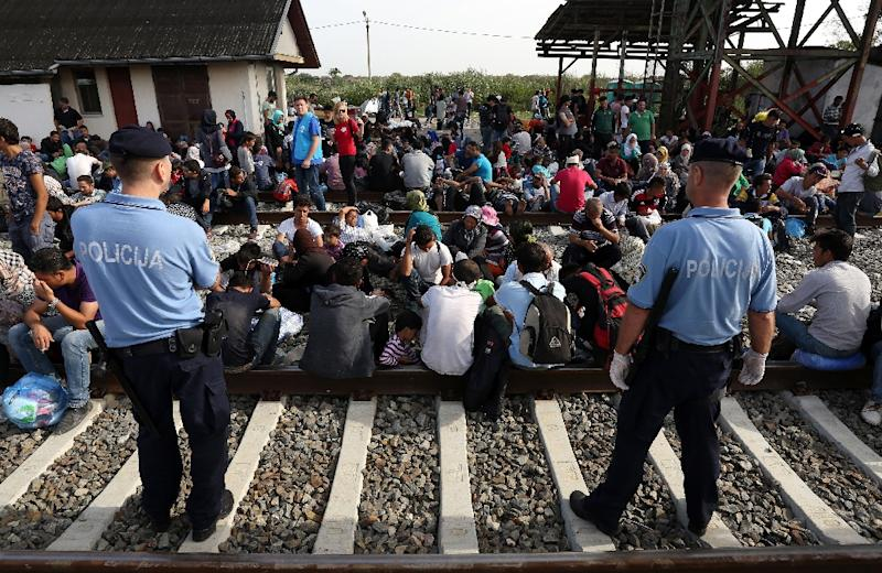 Policemen stand guard as migrants wait at a railway station near the official border crossing between Serbia and Croatia on September 17, 2015 (AFP Photo/)