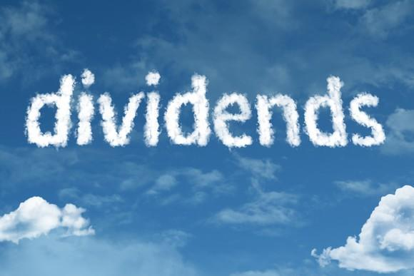 Written in skywriting, the word dividends is set in a partly cloudy sky.