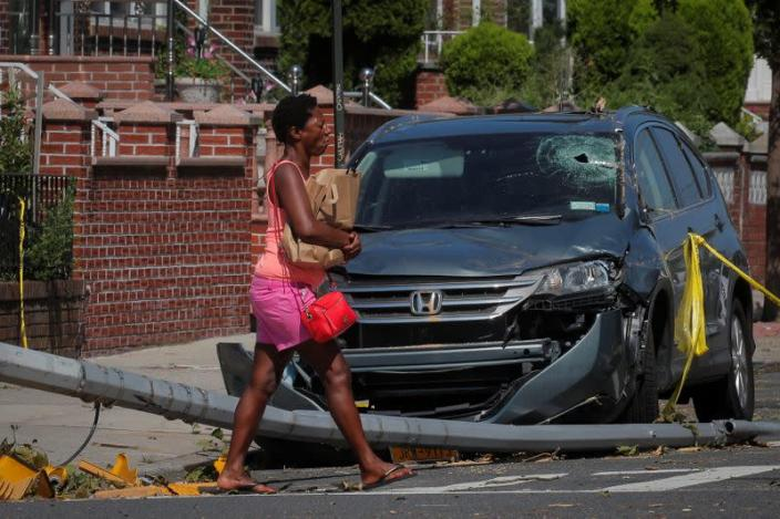 A woman passes by a damaged car and downed pole in the aftermath of Tropical Storm Isaias in the Astoria neighborhood of Queens, New York