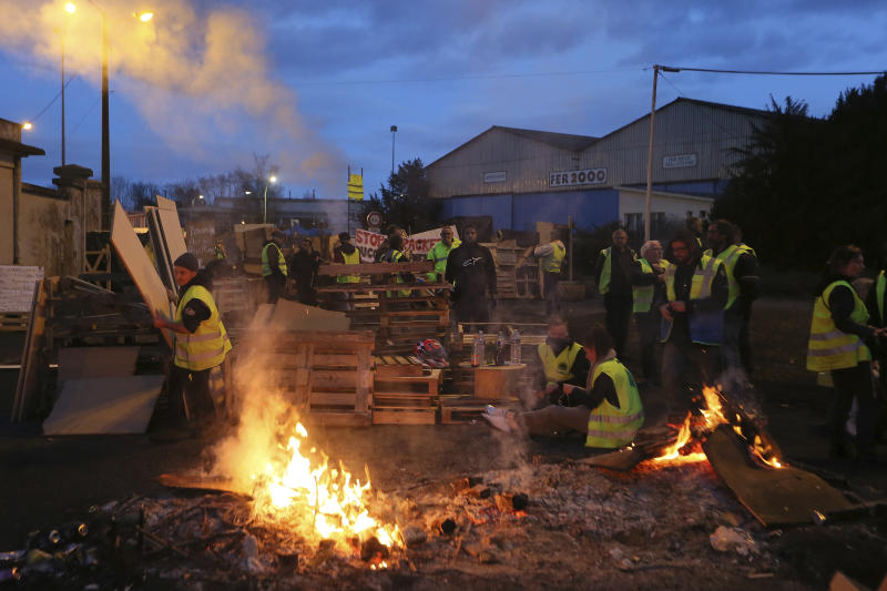 "Demonstrators stand in front of a makeshift barricade set up by the so-called yellow jackets to block the entrance of a fuel depot in Le Mans, western France, Tuesday, Dec. 5, 2018. French government's decision to suspend fuel tax and utility hikes Tuesday did little to appease protesters, who called the move a ""first step"" and vowed to fight on after large-scale rioting in Paris last weekend. (AP Photo/David Vincent)"