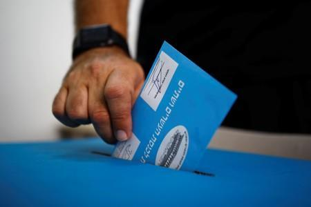 A man casts his vote in a ballot box during Israel's parliamentary election, at a polling station in Tel Aviv, Israel