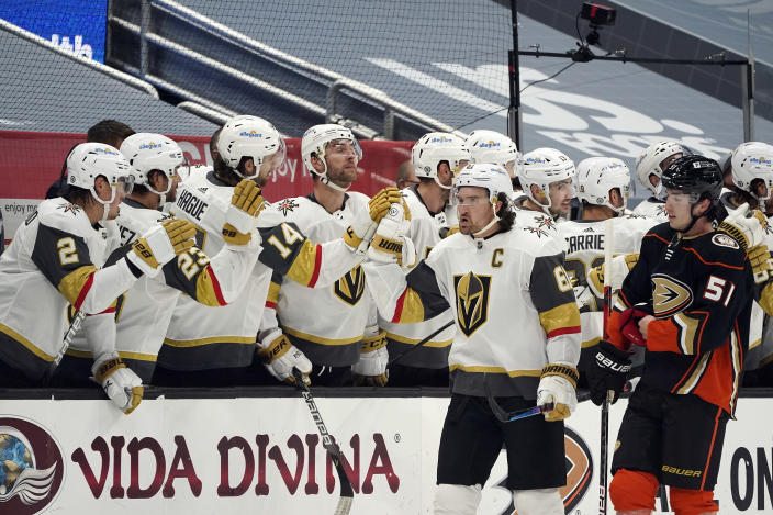 Vegas Golden Knights right wing Mark Stone, center right, high-fives teammates on the bench after scoring during the second period of an NHL hockey game against the Anaheim Ducks, Sunday, April 18, 2021, in Anaheim, Calif. (AP Photo/Marcio Jose Sanchez)