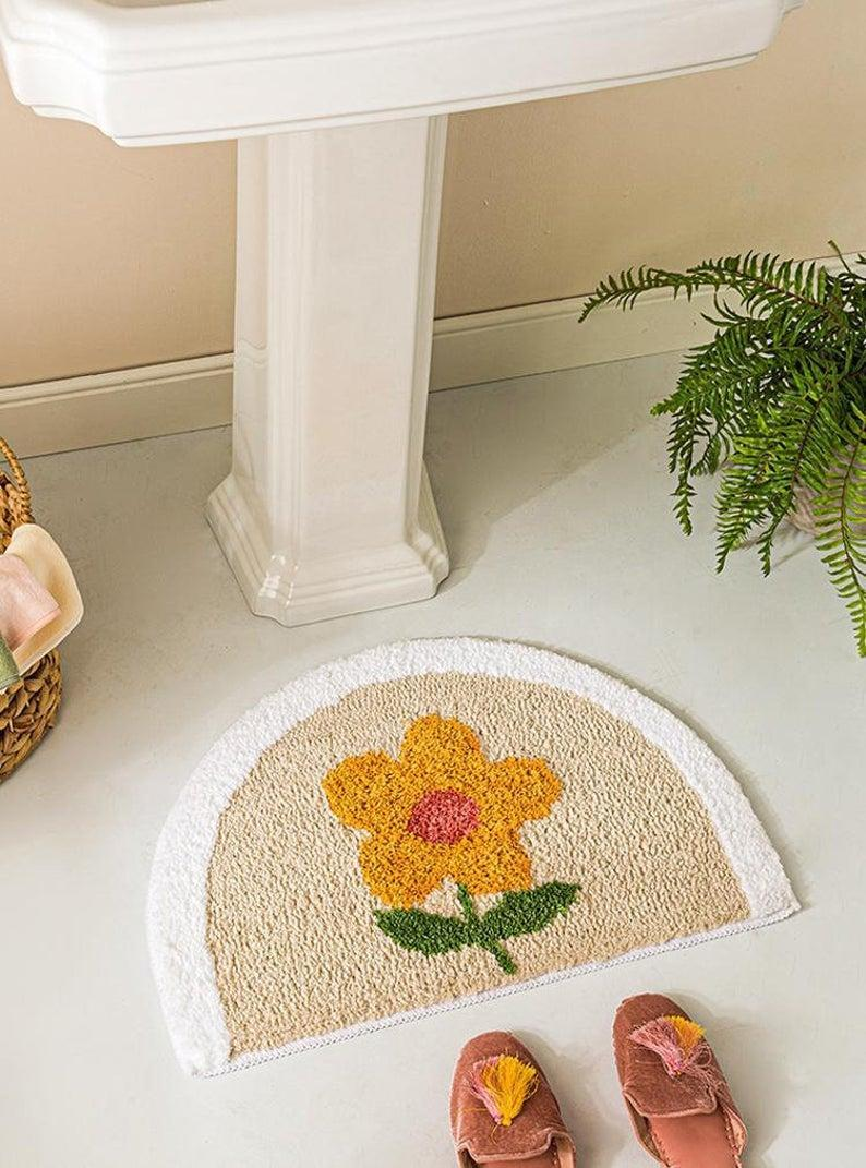 """A bathmat is the ideal space for some tufted creativity. This sweet floral piece is interesting enough to brighten your bathroom without dominating the space.<br><br><strong>Hazindak Store</strong> Bath Mat, 40 x 60cm, $, available at <a href=""""https://www.etsy.com/uk/listing/915484814/bath-mat-bathroom-decor-40-x-60cm?ga_order=most_relevant&ga_search_type=all&ga_view_type=gallery&ga_search_query=tufted+bath+mat&ref=sr_gallery-1-30&organic_search_click=1&frs=1&etp=1"""" rel=""""nofollow noopener"""" target=""""_blank"""" data-ylk=""""slk:Etsy"""" class=""""link rapid-noclick-resp"""">Etsy</a>"""
