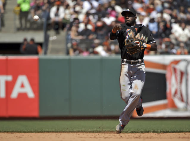 Miami Marlins shortstop Adeiny Hechavarria makes an off-balance throw to put out San Francisco Giants' Hunter Pence at first base during the fifth inning of a baseball game on Sunday, May 18, 2014, in San Francisco. (AP Photo/Marcio Jose Sanchez)