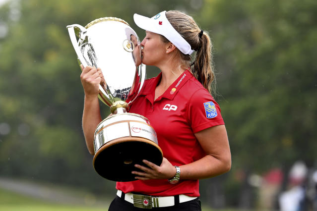 Canada's Brooke Henderson kisses the trophy as she celebrates her win at the CP Women's Open in Regina on Sunday, August 26, 2018. THE CANADIAN PRESS Jonathan Hayward/The Canadian Press via AP)