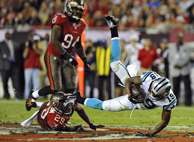 Carolina Panthers wide receiver Ted Ginn (19) is tripped by Tampa Bay Buccaneers cornerback Leonard Johnson (29) after a reception during the second quarter of an NFL football game on Thursday, Oct. 24, 2013, in Tampa, Fla. Buccaneers' Adrian Clayborn (94) chases on the play. (AP Photo/Brian Blanco)