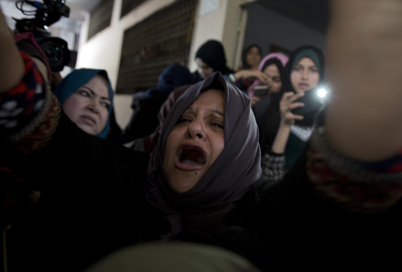 Relatives of Palestinian woman, Amal al-Taramsi, 43, who was killed by Israeli troops during Friday's protest at the Gaza Strip's border with Israel, mourn during her funeral in Gaza City, Saturday, Jan. 12, 2019. (AP Photo/Khalil Hamra)