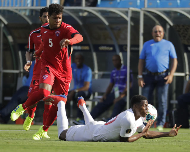 Canada's Jonathan David, right, is fouled by Cuba's Daniel Morejon (5) during the first half of a CONCACAF Golf Cup soccer match in Charlotte, N.C., Sunday, June 23, 2019. (AP Photo/Chuck Burton)