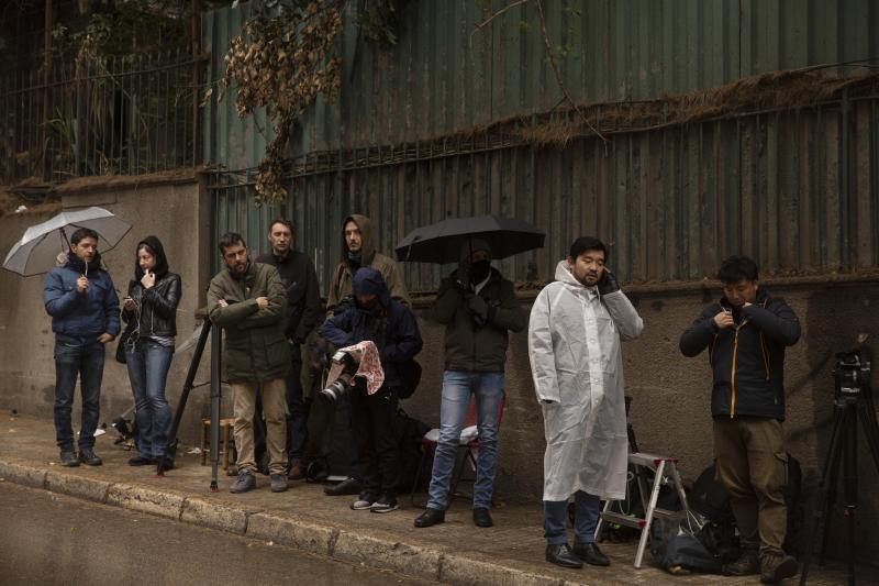Journalists stake out the house of ex-Nissan chief Carlos Ghosn in Beirut, Lebanon, Friday, Jan. 3, 2020. The former Nissan Motor Co. Chairman fled Japan this week while awaiting trial on financial misconduct charges and appeared in Lebanon. (AP Photo/Maya Alleruzzo)