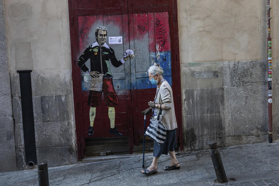 """An elderly woman wearing a face mask to protect against the coronavirus walks past a painting named """"to be or not to be"""" by artist TVBOY and depicting Spanish government's top virus expert Fernando Simon in Madrid, Spain, Sunday, Sept. 13, 2020. (AP Photo/Bernat Armangue)"""