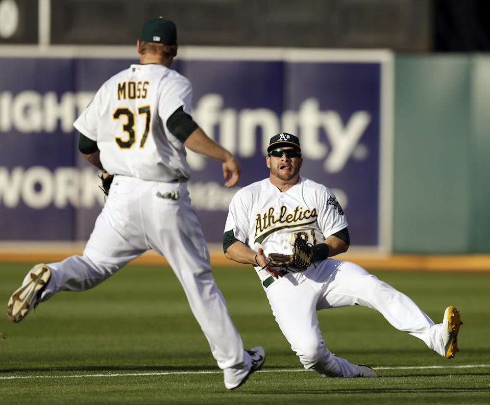 Oakland Athletics' Stephen Vogt, right, catches a ball hit by Boston Red Sox's Xander Bogaerts in the first inning of a baseball game Thursday, June 19, 2014, in Oakland, Calif. Backing up the play is Brandon Moss. (AP Photo/Ben Margot)
