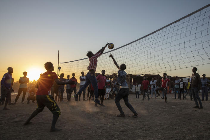 Tigray refugees who fled the conflict in Ethiopia's Tigray region, play volleyball at Um Rakuba refugee camp in Qadarif, eastern Sudan, Monday, Nov. 23, 2020. Tens of thousands of people have fled a conflict in Ethiopia for Sudan, sometimes so quickly they had to leave family behind. There is not enough to feed them in the remote area of southern Sudan that they rushed to. (AP Photo/Nariman El-Mofty)